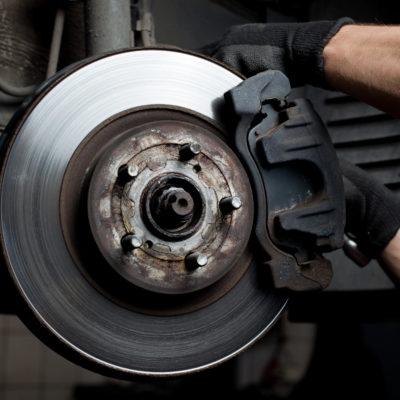 Closeup of car mechanic repairing brake pads